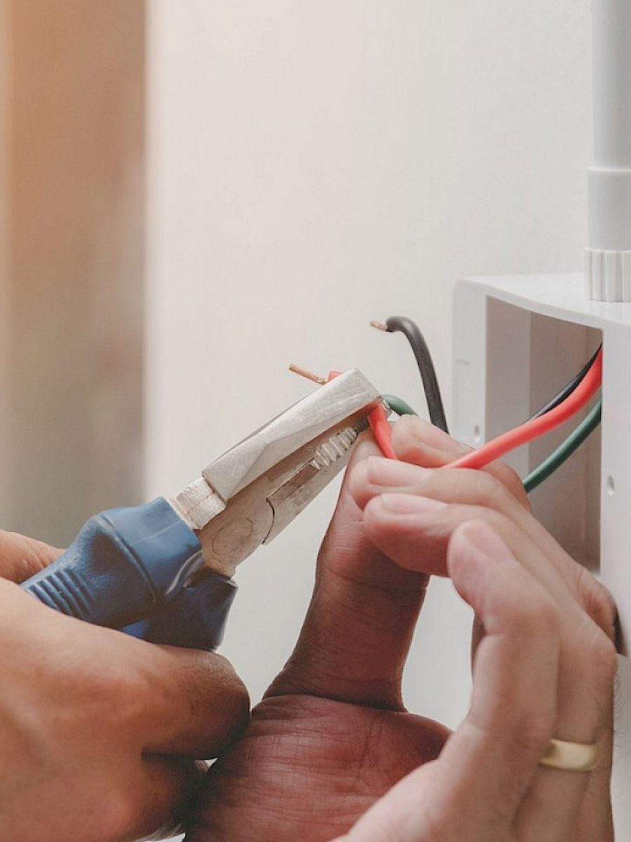 Close up of electricians hands, wiring a socket